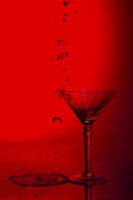 Szklana wysoka fotografia Martini w studiu z czerwonym zabarwieniem i plash wody