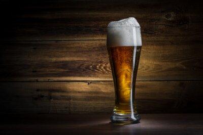 Naklejka Szklanka piwa na drewnianym tle