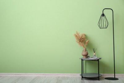 Naklejka Table and floor lamp near color wall