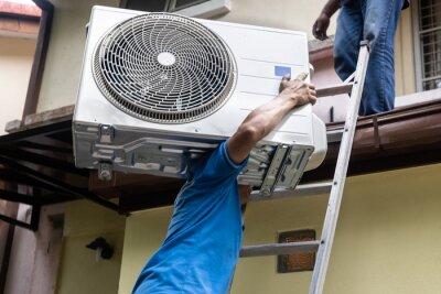Naklejka Technician transporting outdoor air conditioner compressor unit onto roof for installatiion