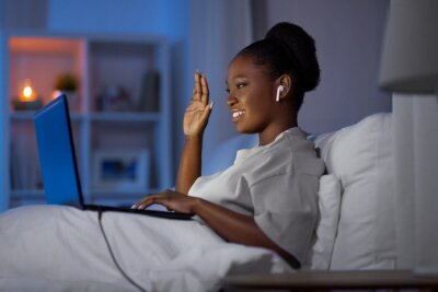 Naklejka technology, internet, communication and people concept - young african american woman with laptop computer and earphones having video call in bed at home at night