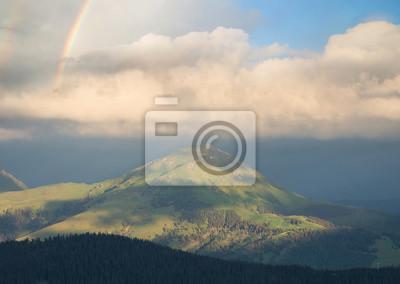 Tęcza pod górami przy deszczem. Piękny naturalny krajobraz