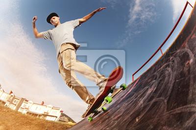 Naklejka Teen łyżwiarka zawiesza się na rampie na deskorolce w parku łyżwiarstwie