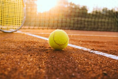 Naklejka Tennis racket and ball on a clay court