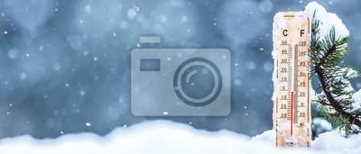 Naklejka Termometr na śniegu pokazuje niskie temperatury w stopniach Celsjusza lub Farenheit