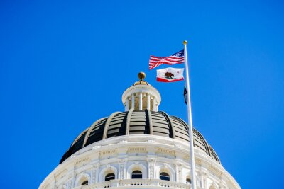 Naklejka The US and the California state flag waving in the wind in front of the dome of the California State Capitol, Sacramento, California