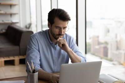 Naklejka Thoughtful serious male freelancer sit at table work on computer look at screen pondering or making decision. Pensive man employee worker busy at laptop, brainstorm think over problem solution.