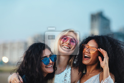 Naklejka Three beautiful women with colorful sunglasses standing at evening outdoors