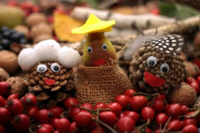 Three faces made of cones with eyes and mouth, head cover surounded by falll items as rose hip, nuts, grapes, leaves. Autumn background.