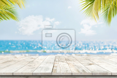 Naklejka Top of wood table with seascape and palm leaves, blur bokeh light of calm sea and sky at tropical beach background. Empty ready for your product display montage.  summer vacation background concept.