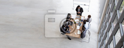 Naklejka Top view of group of multiethnic busy people working in an office, Aerial view with businessman and businesswoman sitting around a conference table with blank copy space, Business meeting concept