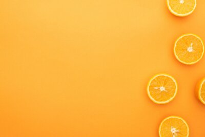 Naklejka top view of juicy orange slices on colorful background