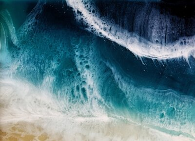 Naklejka Top view on sea wave with white foam and light beige sand. drawing with epoxy resin. Close-up of deep rich blue, azure, turquoise color of water, shore. Trendy painting for background