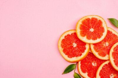 Naklejka top view tasty grapefruits juicy fruit slices on pink background mellow color diet citrus juice fruit fresh