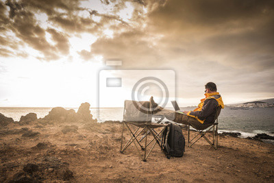 Naklejka Travel and enjoying outdoor people concept with lonely man working on laptop internet connecetd computer sitting in front of an amazing sunset on the ocean - digital nomad millennial concept
