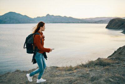 Naklejka traveler in a sweater with a backpack in jeans and sneakers on the beach near the sea in the mountains