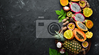 Naklejka Tropical fruits: papaya, mangosteen, cactus fruit, pytahaya, pineapple on a black background. Top view. Free space for text.