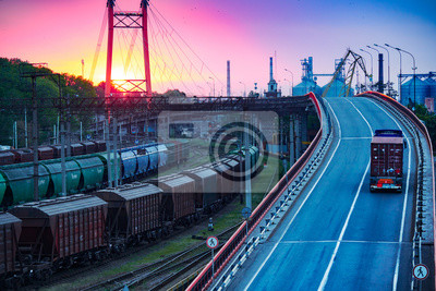 Naklejka truck with container rides on the road, railroad transportation, freight cars in industrial seaport at sunset