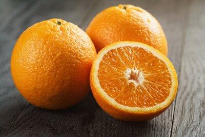 Naklejka trzy dojrzałe pomarańcze na drewnianym stole jeden pół cięcia