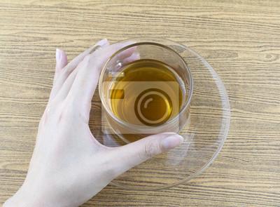 Naklejka Trzyma kubek herbaty szkło