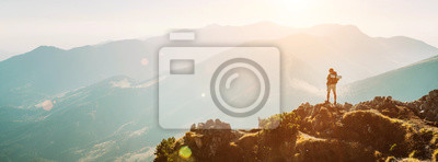 Naklejka Turysta z plecakiem malutka figurka zostaje na szczycie góry z piękną panoramą