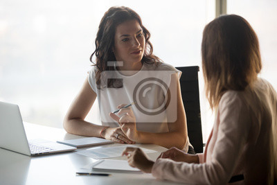 Naklejka Two diverse serious businesswomen discussing business project working together in office, serious female advisor and client talking at meeting, focused executive colleagues brainstorm sharing ideas