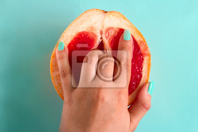 Naklejka two fingers in a grapefruit isolated on a blue background top view sex concept