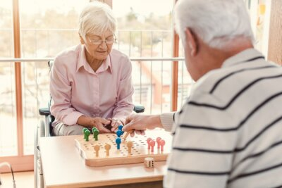 Naklejka Two seniors in a nursing home playing a board game
