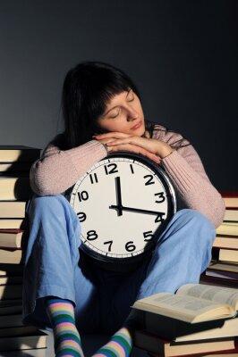 uczeń zasnął na stosie książki, podczas gdy robi swoje zadanie domowe.