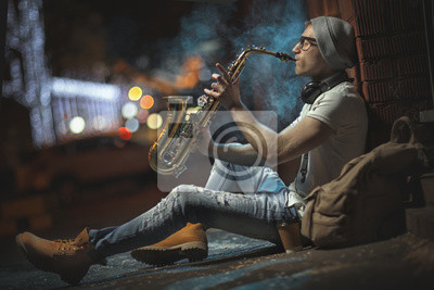 Naklejka Uliczny muzyk gra na saksofonie w wieczornym mieście