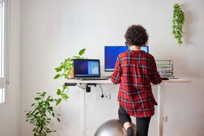 Naklejka Unrecognizable woman teleworking at an adjustable standing desk