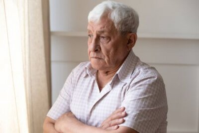 Naklejka Upset old man look in window distance feel lonely and distressed thinking missing past days, thoughtful upset mature male lost in thoughts mourning yearning, remembering, elderly solitude concept