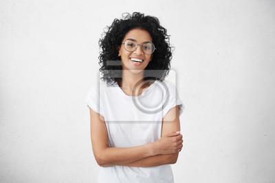 Naklejka Uroczy młoda kobieta o ciemności skóry z kręcone fryzurę z nieśmiałym uśmiechem pozując w studio w zamkniętej pozycji, trzymając ręce złożone, czując się ograniczony i trochę zdenerwowany. Ludzkie emo