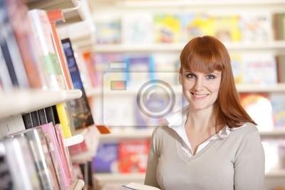 uśmiecha się młoda studentka w bibliotece