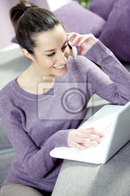 Uśmiechnięta kobieta na kanapie z laptopa i telefon komórkowy