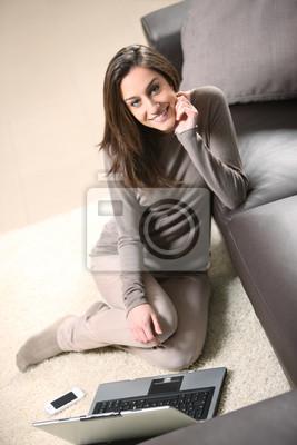 Uśmiechnięta kobieta przy użyciu swojego laptopa w salonie.