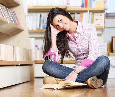 uśmiechnięta kobieta student siedzi na podłodze w bibliotece, przeczytaj