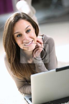 Uśmiechnięta kobieta, używając swojego laptopa w salonie.