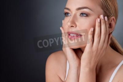 Naklejka uśmiechnięta kobieta z odkrytymi ramionami dotykając twarzy