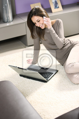 Uśmiechnięta kobieta z telefonu komórkowego i laptopa