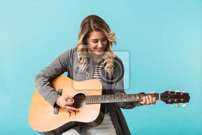 Naklejka Uśmiechnięta młoda dziewczyna bawić się gitarę podczas gdy siedzieć odizolowywam