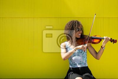 Naklejka Uśmiechnięta młoda kobieta gra na skrzypcach na zewnątrz