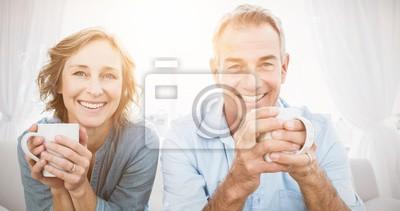 Naklejka Uśmiechnięta para w średnim wieku siedzi na kanapie kawie