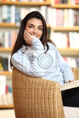 uśmiechnięta studentka z książką w ręce patrząc na kamery. Na
