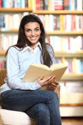 uśmiechnięta studentka z książką w ręce siedzi w fotelu w