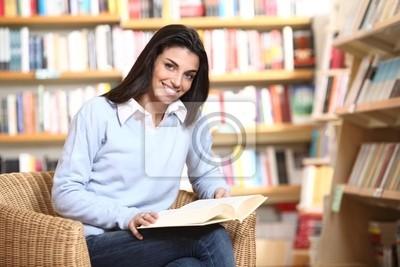Naklejka uśmiechnięta studentka z książką w ręce siedzi w fotelu w
