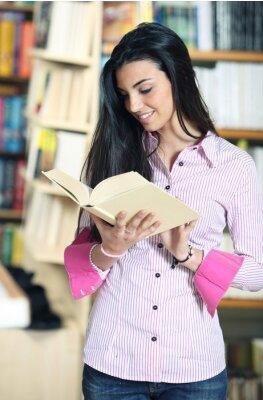 uśmiechnięta studentka z książką w ręce w księgarni