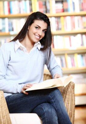 uśmiechnięta studentka z książką w ręce w księgarni - modelu
