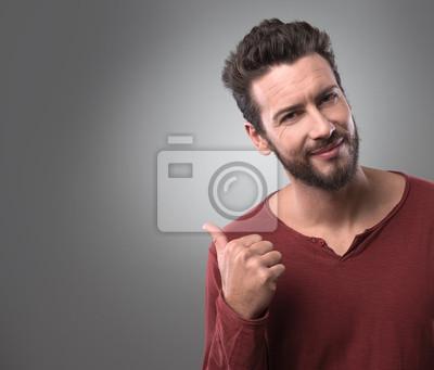 Uśmiechnięty młody człowiek wskazując