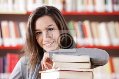 uśmiechnięty student z stos książek